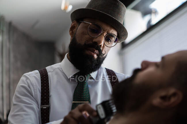 Stylish mature dandy ethnic male beauty master cutting mustache of bearded client using trimmer in barbershop — Fotografia de Stock
