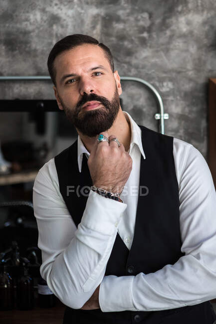 Adult brutal male executive in formal wear and rings touching beard while looking at camera in hairdressing salon — стоковое фото
