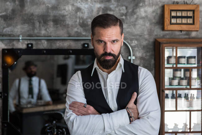 Adult brutal male executive in formal wear and rings looking at camera in hairdressing salon — Stock Photo