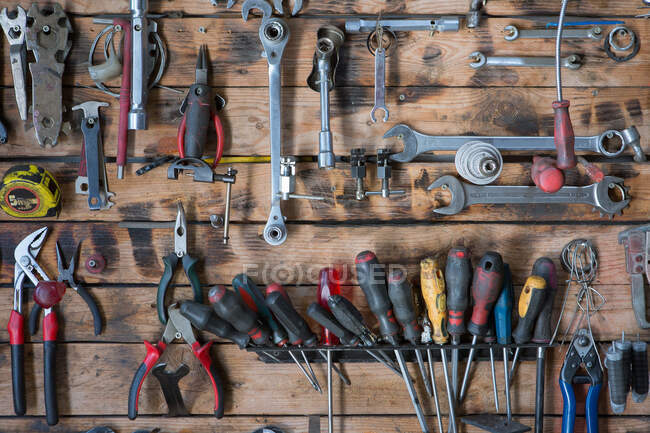 Set of different iron instruments for repairing on lumber wall in modern workshop — Stock Photo
