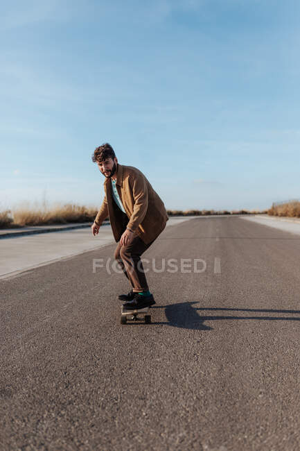 Full body young bearded male skater in stylish wear riding skateboard along asphalt road in countryside — Foto stock