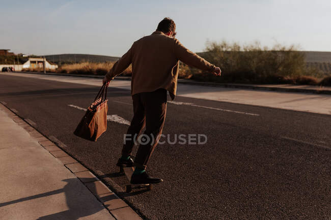Full body back view of unrecognizable male skater in trendy clothes with leather bag riding skateboard along asphalt road — Foto stock