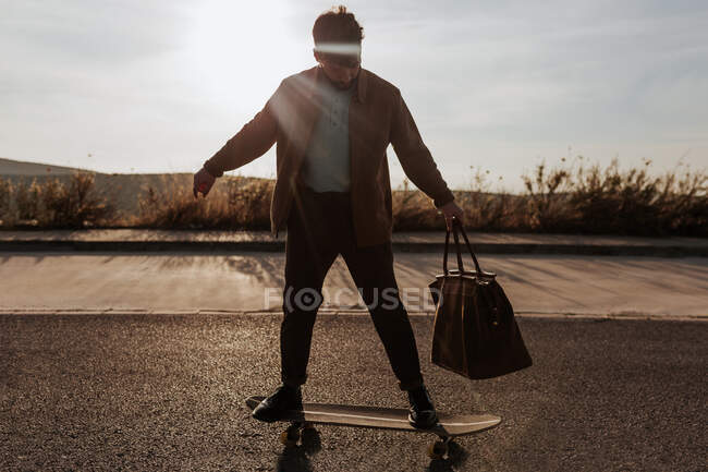 Full body serious young bearded male skater in trendy clothes with leather bag riding skateboard along asphalt road — Fotografia de Stock
