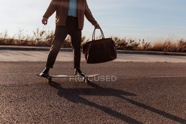 Cropped unrecognizable male skater in trendy clothes with leather bag riding skateboard along asphalt road — Foto stock