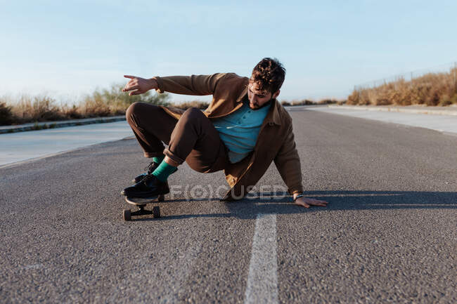 Full body young bearded male skater in casual clothes performing trick touching ground while riding on asphalt road — Foto stock