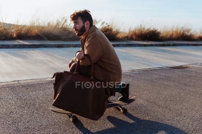 Side view of full body serious young bearded male skater in trendy clothes with leather bag riding skateboard along asphalt road — Foto stock