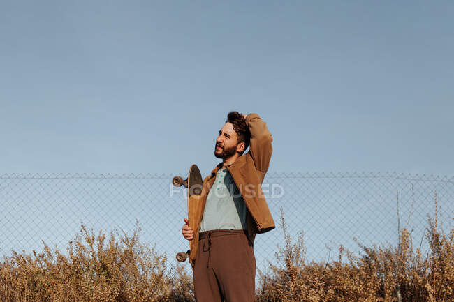Smiling young bearded male skater in casual wear standing near grass and fence with skateboard and touching hair looking away — Stock Photo