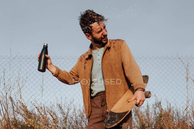 Young bearded male skater with closed eyes in casual outfit pouring water from bottle on head standing near fence in countryside — Foto stock