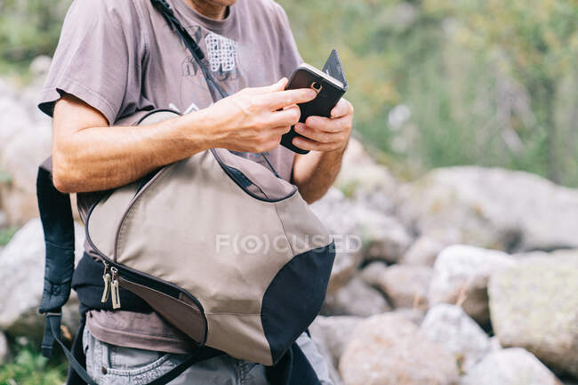 Crop anonymous male trekker in sunglasses browsing on smartphone during trip — стоковое фото