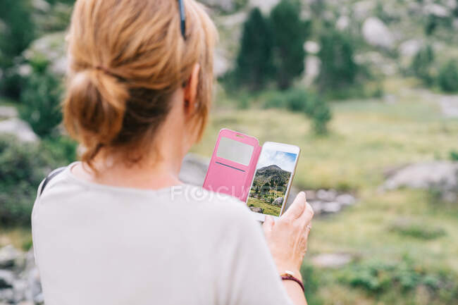 Back view anonymous female taking pictures on smartphone of amazing stony verdant highlands in Ruda Valley in Catalan Pyrenees — Stock Photo