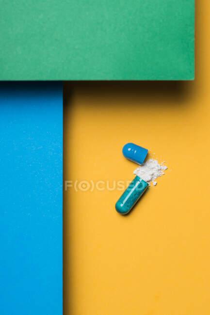 Alto ángulo de contenido de la droga médica vertida de la cápsula de color azul sobre el fondo amarillo - foto de stock