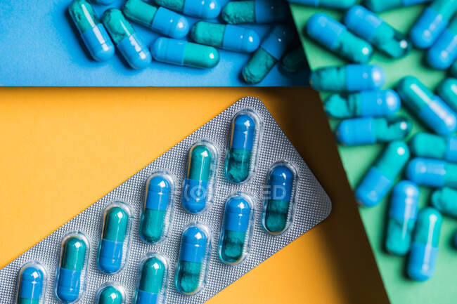 Envases blíster de plástico con cápsulas médicas azules colocadas sobre fondo amarillo, verde y azul - foto de stock
