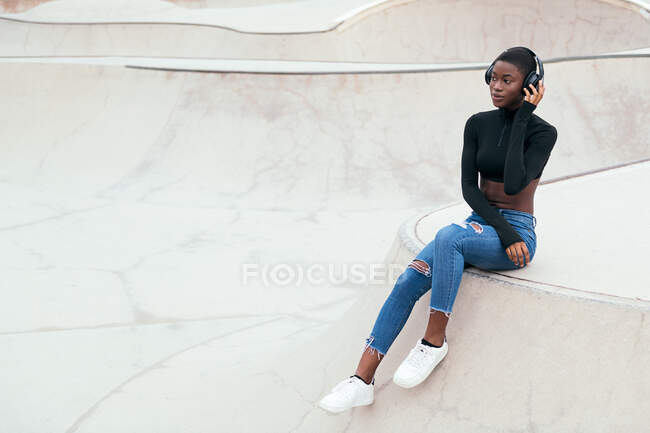 Side view of young contemplative African American female in ripped jeans listening to music from wireless headphones while looking forward — Stock Photo