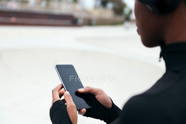 Crop anonymous ethnic female text messaging on mobile phone with black screen in city — Stock Photo
