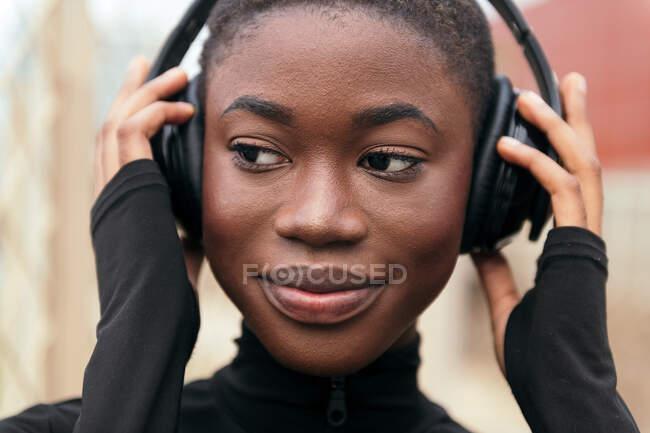Обрезание молодых мечтательных черных женщин слушать музыку из беспроводных наушников, глядя в сторону при дневном свете — стоковое фото