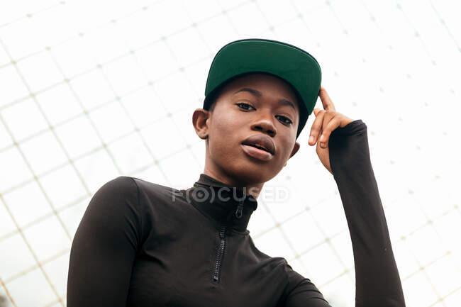 Angolo basso di giovane donna afroamericana in abbigliamento casual guardando la fotocamera con il dito in alto alla luce del giorno — Foto stock