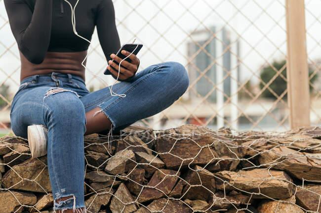 Crop femme noire écouter de la musique avec un téléphone portable et écouteurs — Photo de stock