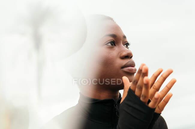 Jeune femme contemplative ethnique aux cheveux courts touchant le visage en plein jour — Photo de stock