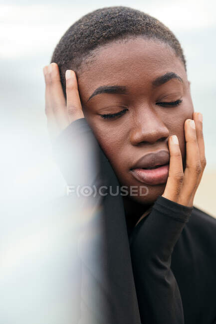 Молодая созерцательная этническая женщина с закрытыми глазами и короткими волосами, касающимися лица при дневном свете — стоковое фото