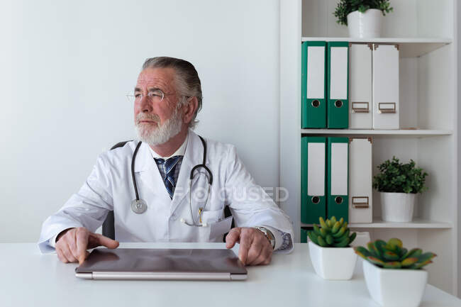 Dreamy elderly male doctor in eyeglasses with stethoscope looking away at table with tablet in hospital — Stock Photo