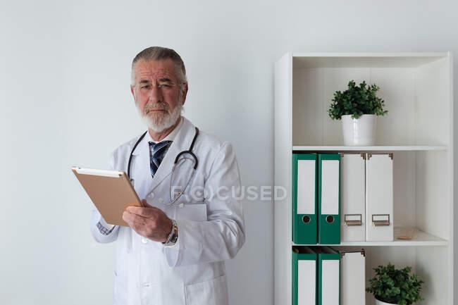 Médico idoso grave em óculos com estetoscópio a olhar para a câmara e a segurar o comprimido no hospital — Fotografia de Stock