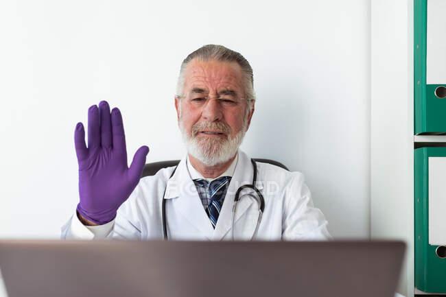 Médico senior con guantes uniformados y estériles mostrando gesto de saludo contra netbook durante una videollamada en el hospital - foto de stock