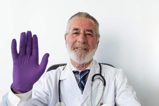 Senior medico di sesso maschile con in uniforme e guanti sterili mostrando gesto di saluto contro netbook durante la videochiamata in ospedale — Foto stock