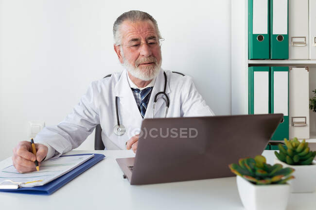 Médico sênior em uniforme escrevendo memorandos no papel durante consulta de saúde on-line no computador portátil no hospital — Fotografia de Stock