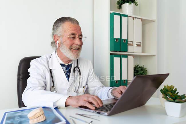 Hombre ortodoncista mayor hablando en contra de netbook durante el chat de vídeo en la mesa en el hospital - foto de stock