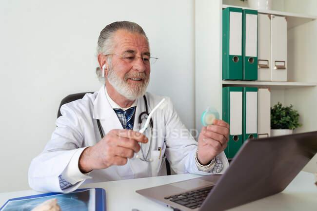Ortodontista do sexo masculino sênior mostrando escova de dentes e fio dental enquanto fala contra netbook durante vídeo chat na mesa no hospital — Fotografia de Stock