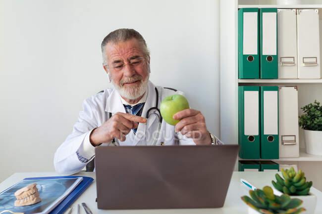 Ortodontista idoso do sexo masculino mostrando maçã verde contra computador portátil enquanto faz videochamada na clínica — Fotografia de Stock