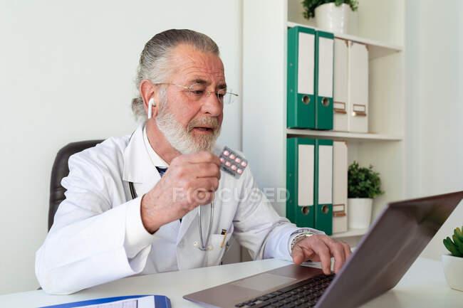Anciano médico varón en auricular que muestra medicamentos mientras habla en el chat de vídeo contra netbook durante la consulta de salud en línea en el hospital - foto de stock