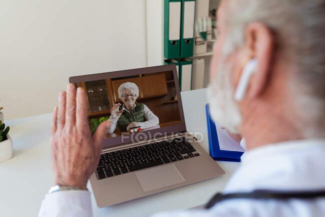 Visão traseira da cultura anônimo idoso médico masculino em fone de ouvido sem fio falando com mulher em chamada de vídeo no netbook na clínica — Fotografia de Stock