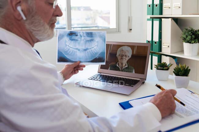 Seitenansicht eines älteren männlichen Arztes im drahtlosen Ohrhörer, der mit einer Frau auf einem Netbook in der Klinik spricht — Stockfoto