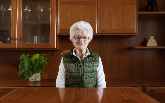 Старшая пенсионерка с седыми волосами в очках и жилете, смотрящая в камеру на деревянный стол в доме — стоковое фото