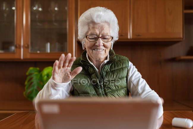 Friendly elderly female in wireless earbuds showing greeting gesture against tablet while video chatting in house — Stock Photo