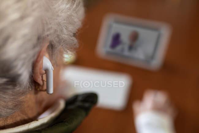 Сверху спины просматривается анонимная пожилая женщина в наушниках TWS, разговаривающая с врачом на планшете во время видеозвонка домой — стоковое фото