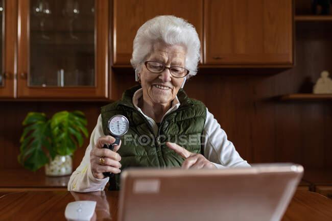 Улыбающаяся пожилая пенсионерка указывает на сфигмоманометр, разговаривая в видеочате с планшетом во время онлайн консультации по здоровью дома — стоковое фото