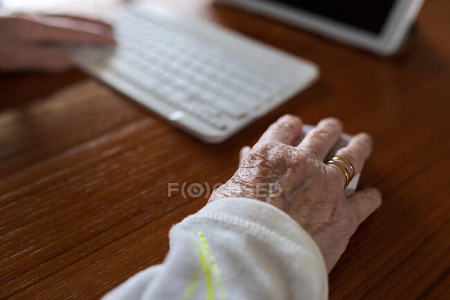 Recorte paciente anónimo con teclado contra tableta con médico en pantalla durante la videollamada en casa - foto de stock