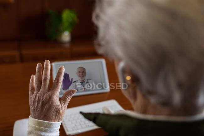 De cima vista traseira de cultura anônimo idoso paciente feminino em fones de ouvido TWS falando com o médico em tablet durante videochamada em casa — Fotografia de Stock