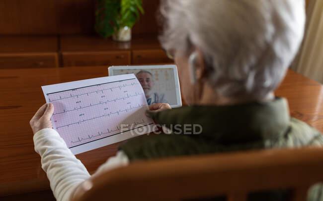 Обратный просмотр анонимной урожая женщины-пенсионера с электрокардиограммой на бумаге на фоне планшета с врачом на экране во время онлайн консультации по здоровью на дому — стоковое фото