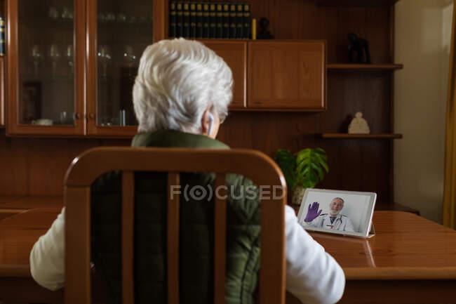 Visão traseira da paciente idosa anônima em fones de ouvido TWS falando com o médico em tablet durante videochamada em casa — Fotografia de Stock