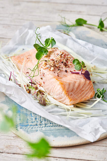 Delicious fish fillet with green pea sprouts and seasonings on baking paper on table in daytime — Stock Photo