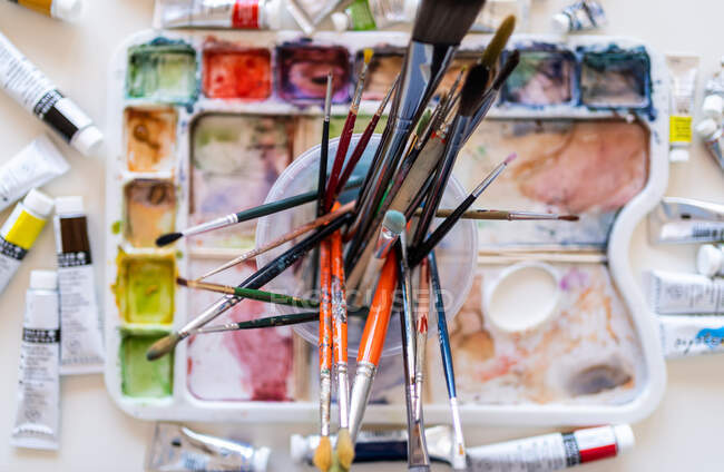 High angle multicolored paintbrushes of different sizes placed on watercolor palette — Stock Photo