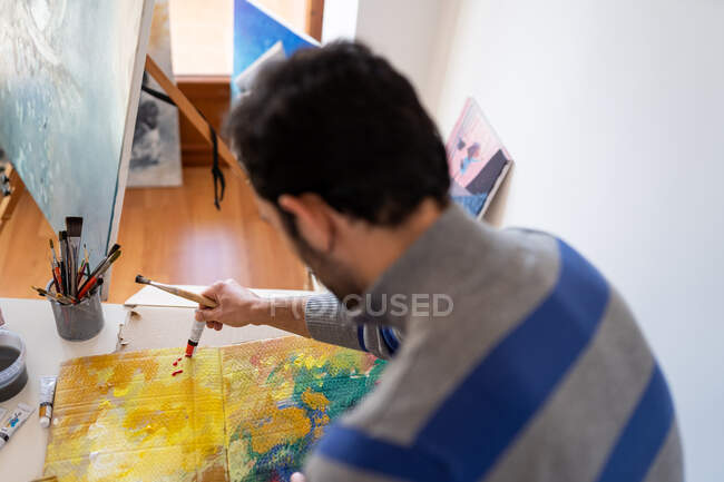 Crop unrecognizable male painter using professional brush during painting process on carton sheet near art tools in workroom - foto de stock
