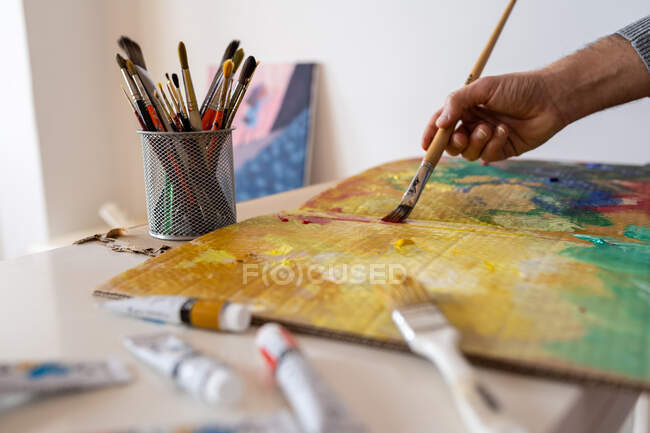 Crop unrecognizable male painter using professional brush during painting process on carton sheet near art tools in workroom — Foto stock
