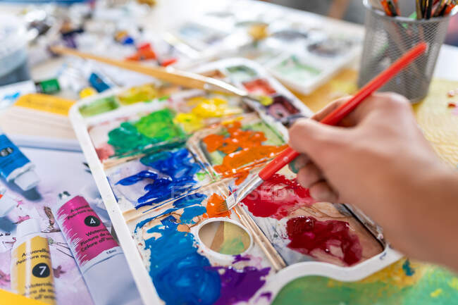 Crop anonymous painter mixing paints with brush using watercolor palette while working in art studio — Stock Photo
