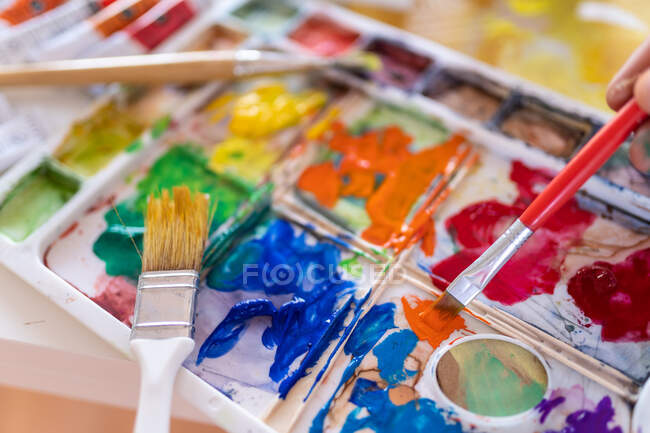 Crop anonymous painter mixing paints with brush using watercolor palette while working in art studio — Foto stock