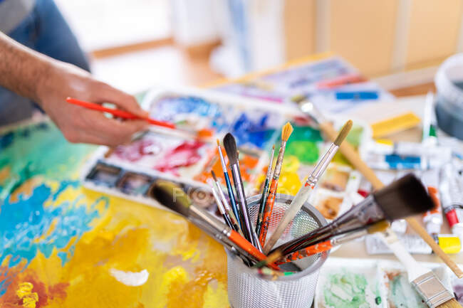 Crop anonymous male painter mixing paints with brush using watercolor palette while working in art studio — Stock Photo