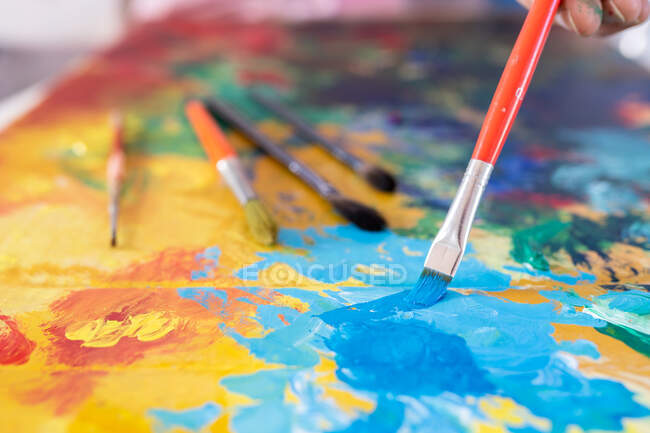Crop unrecognizable male painter using professional brush during painting process on carton sheet near art tools in workroom — Stock Photo